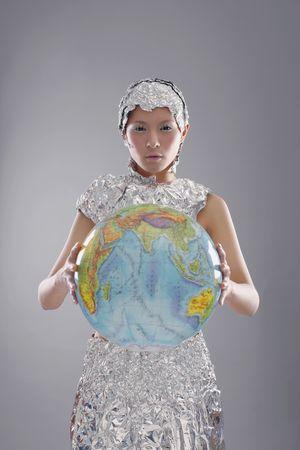 quarter foil: Woman wearing foil accessories holding globe Stock Photo