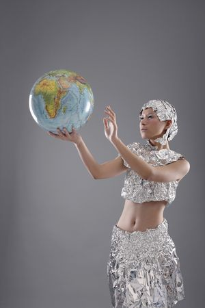 Woman wearing foil accessories holding globe Stock Photo