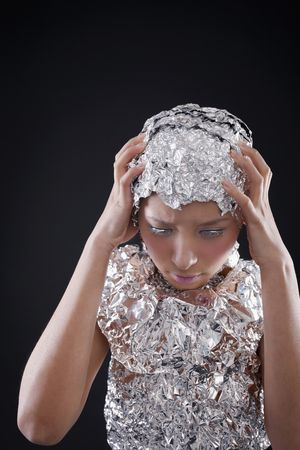 Woman wearing foil accessories with head in her hands Stock Photo