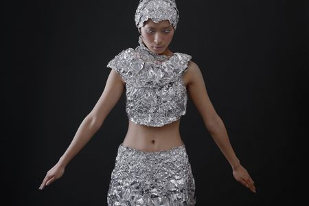 quarter foil: Woman wearing foil accessories with head bent down