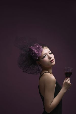 Woman with net and flower decorating her hair holding wine glass photo