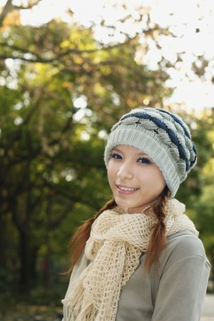 Woman wearing scarf and knit hat smiling Stock Photo