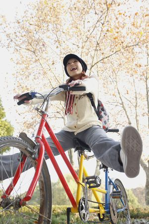 Woman riding tandem bicycle with legs outstretched Stock Photo - 10296417