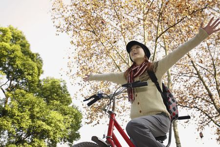 Woman riding tandem bicycle with arms outstretched