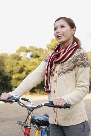 Woman holding tandem bicycle, smiling