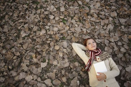 Woman holding book lying on ground covered with dried leaves Stock Photo - 10296403
