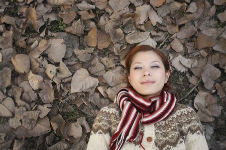 eyes closing: Mujer tendida en el suelo cubierto de hojas secas, cerrando los ojos Foto de archivo
