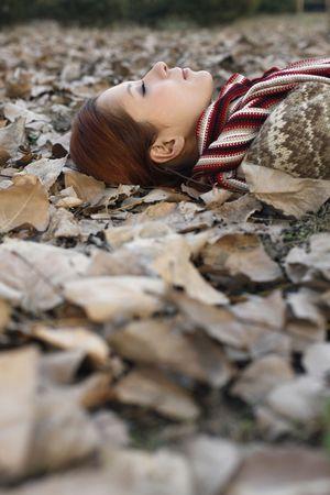 eyes closing: Mujer tendida en el suelo cubierto de hojas secas, cerrar los ojos Foto de archivo