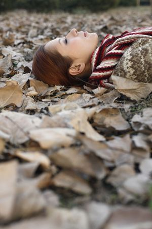 closing eyes: Woman lying on ground covered with dried leaves, closing eyes Stock Photo