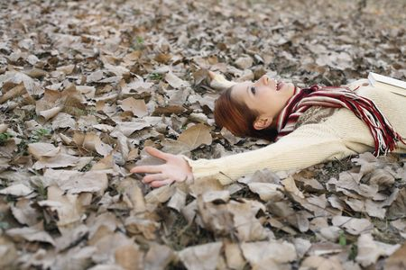 outstretched arms: Woman lying on ground covered with dried leaves with arms outstretched Stock Photo