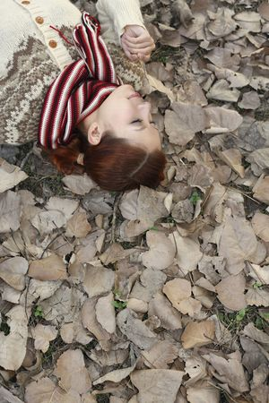 Woman lying on ground covered with dried leaves, smelling leaf