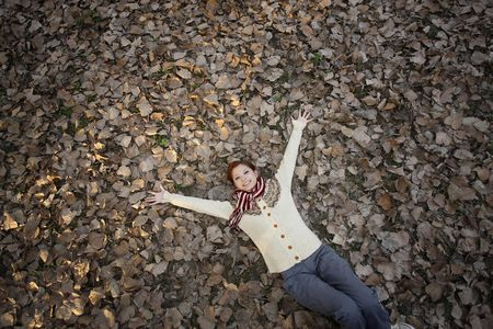 Woman lying on ground covered with dried leaves with arms outstretched Stock Photo