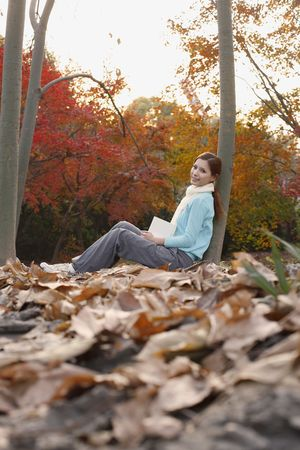 Woman leaning against tree holding book