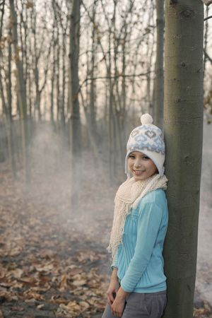 Woman wearing knit hat and scarf leaning against tree, smiling