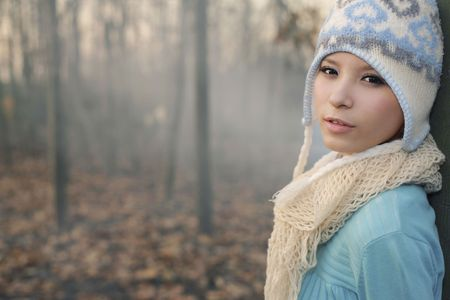 Woman wearing knit hat and scarf leaning against tree