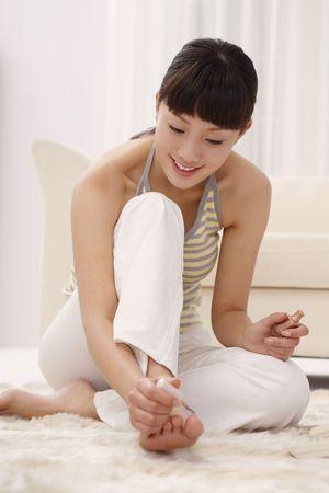 Woman applying nail polish photo