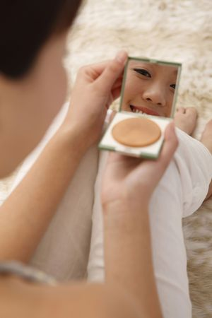 full length mirror: Woman looking at compact mirror