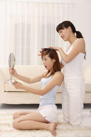 curlers: Woman looking at mirror while friend curling her hair Stock Photo