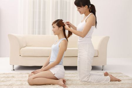 chinese adult: Woman combing hair for her friend