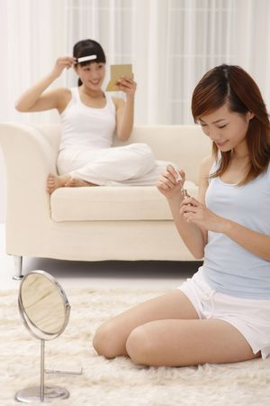 full length mirror: Woman applying nail polish, another woman combing her fringe in the background Stock Photo