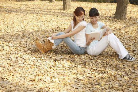 Women reading book together photo