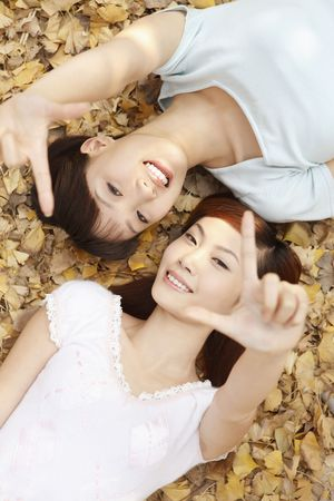 bonding: Women showing finger signal while lying on the ground Stock Photo