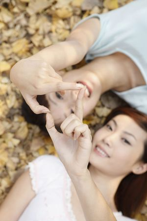 Women making heart shape with fingers Stock Photo