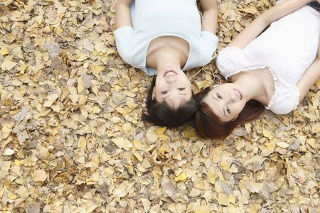 Women lying on the ground listening to music on portable MP3 player Stock Photo
