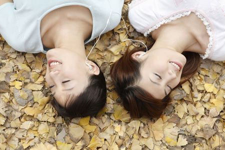 Women lying on the ground listening to music on portable MP3 player Stock Photo - 10294956