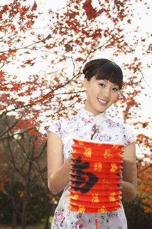 Woman in cheongsam holding lantern