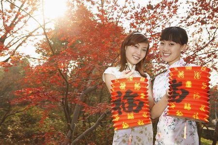 Women in cheongsam holding lanterns Stock Photo