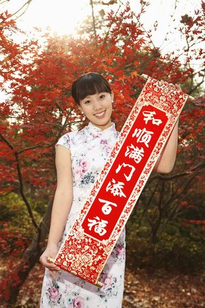 Woman in cheongsam holding banner photo