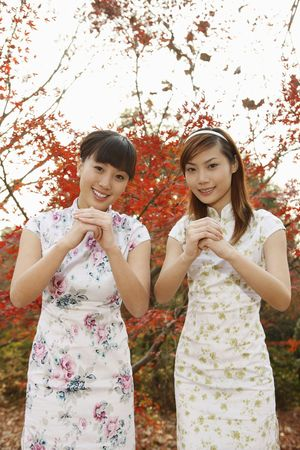Women in cheongsam greeting with their hands clasped together photo