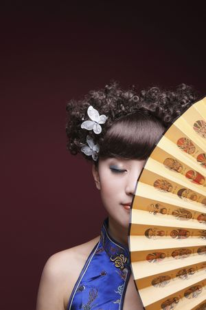 Woman in cheongsam covering part of her face with fan, eyes closed Stock Photo - 10295526