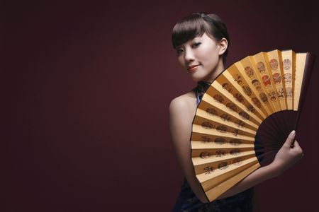 cheongsam: Woman in cheongsam posing with fan