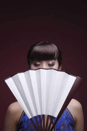 Woman in cheongsam covering part of her face with fan, eyes closed