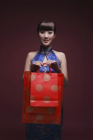 Woman in cheongsam carrying paperbags
