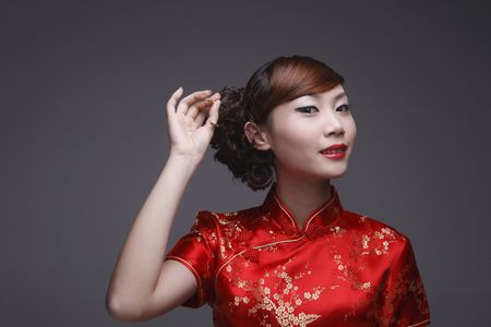 cheongsam: Woman in red cheongsam pulling out hair pin from her hair Stock Photo
