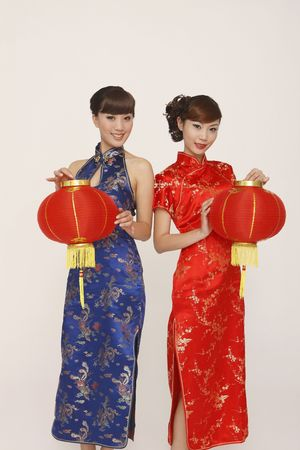 Women in cheongsam holding lanterns Stock Photo