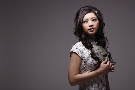 Woman in cheongsam holding fan photo