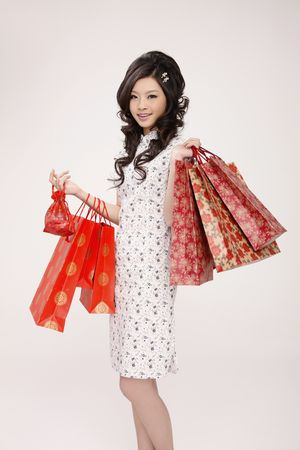 Woman in cheongsam carrying paperbags Stock Photo - 10294685