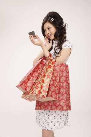 Woman looking at compact mirror while carrying paperbags Stock Photo - 10294195