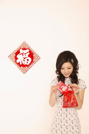 Woman in cheongsam taking out red packet from the bag Stock Photo