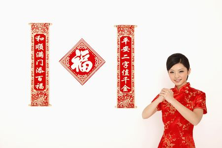Woman in red cheongsam with greeting gesture Stock Photo