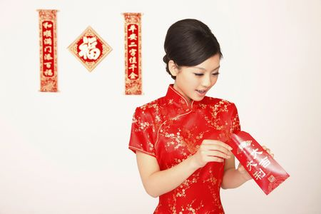 Woman in cheongsam checking the content of red packet