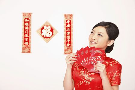 red head woman: Woman smiling while holding red packets