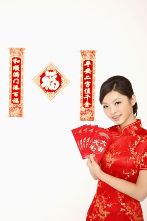 Woman in cheongsam holding red packets and posing
