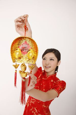 traditional celebrations: Woman hanging chinese new year decorative item