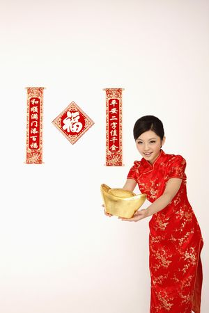 Woman in cheongsam holding a big gold ingot