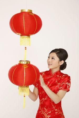Woman in red cheongsam admiring the hanging lantern Stock Photo